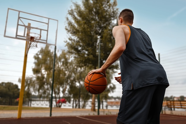 Basketball player prepares to make a throw on outdoor court.