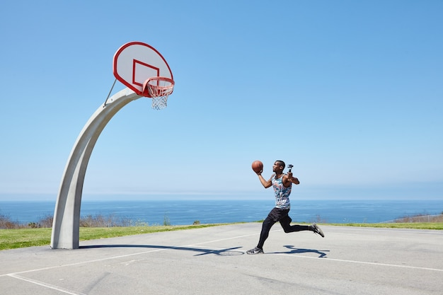 Basketball player running by the ocean with selfie camera