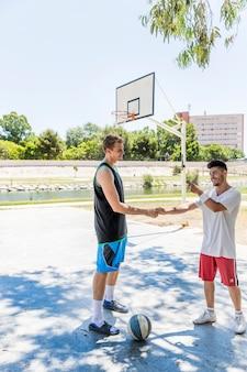 屋外のバスケットボールコートでお互いの手を振ってバスケットボール選手