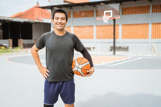 手でバスケットボールを持って笑っているバスケットボール選手