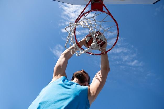 농구 선수. 스포츠와 농구. 한 젊은이가 점프하여 바구니에 공을 던졌습니다. 푸른 하늘과 백그라운드에서 법원입니다.