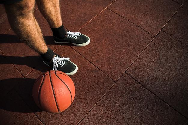 Basketball player standing next to basketball