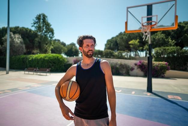 夏に屋外のバスケットボールコートに立っているバスケットボール選手