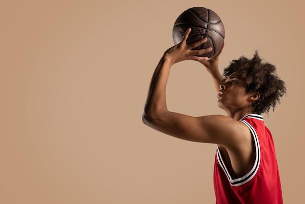 バスケットボール選手がボールを投げる Premium写真