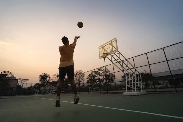 地元のコートで屋外でトレーニングとエクササイズをするバスケットボール選手