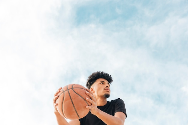 Basketball player with ball looking away