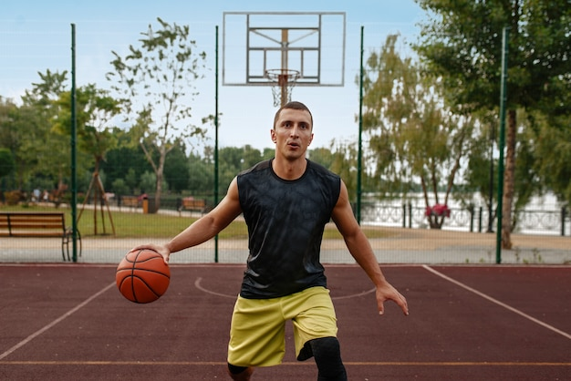 Basketball player with ball in motion on outdoor court.
