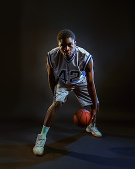 Basketball player with ball, practicing in action. professional male baller in sportswear playing sport game, tall sportsman