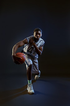 Basketball player with ball, practicing in action in studio, black background. professional male baller in sportswear playing sport game, sportsman