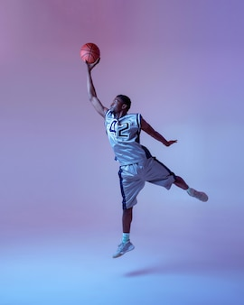 Basketball player with ball shows his skill, jump in action. professional male baller in sportswear playing sport game, tall sportsman