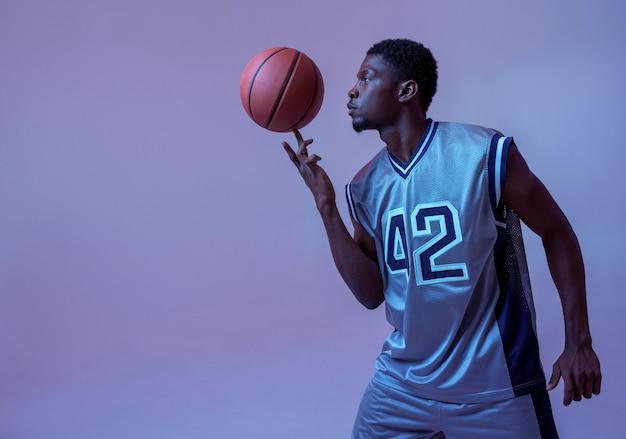 ボールを持ったバスケットボール選手は彼のスキルを示しています。スポーツゲームをするスポーツウェアのプロの男性バラー、背の高いスポーツマン