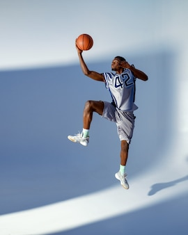 Basketball player with ball shows his skill in studio, high jump in action, neon background. professional male baller in sportswear playing sport game, tall sportsman