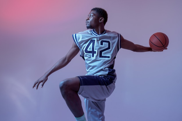 Basketball player with ball shows his skill in studio, jump in action, neon background. professional male baller in sportswear playing sport game, tall sportsman