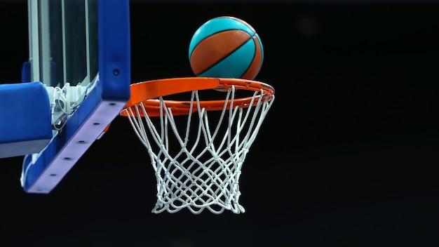 Баскетбольное кольцо с сеткой, в которой мяч летит на темном фоне