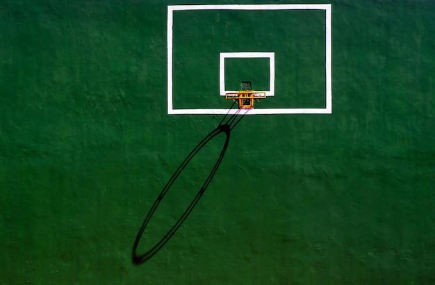 녹색 시멘트 벽에 그림자가 있는 농구 링