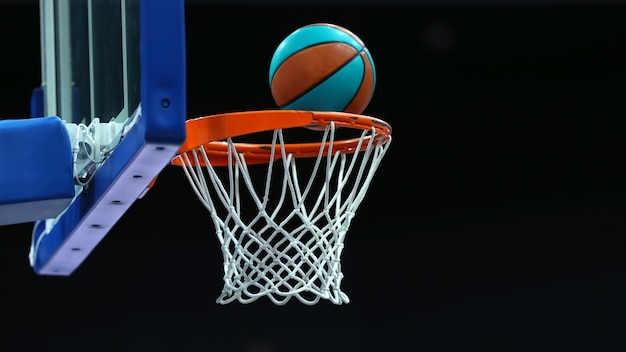 Basketball ring with a net in which the ball flies on a dark background