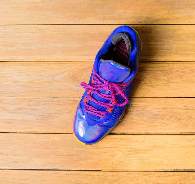 Basketball sport shoes or sneakers on wooden board