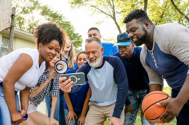 チームを見ているバスケットボールサポーターが携帯電話で試合に勝つ