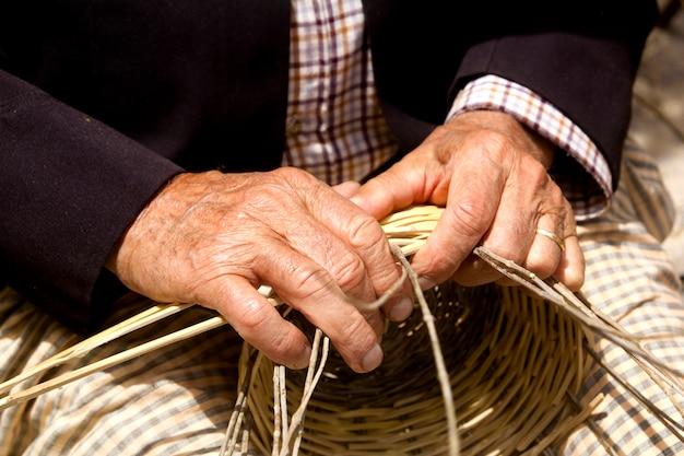 Basketry craftsman hands working in mediterranean basket
