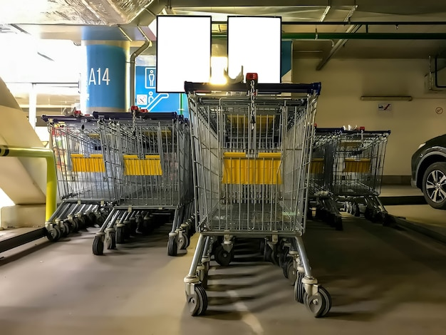 Baskets or carts for food and goods located in underground parking of shopping center, supermarket. straight rows of shopping carts stand at entrance to store. copyright space