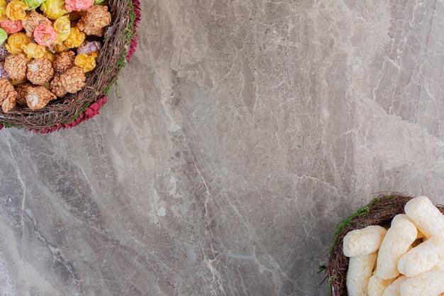 Cesti di snack di mais e caramelle popcorn su marmo.