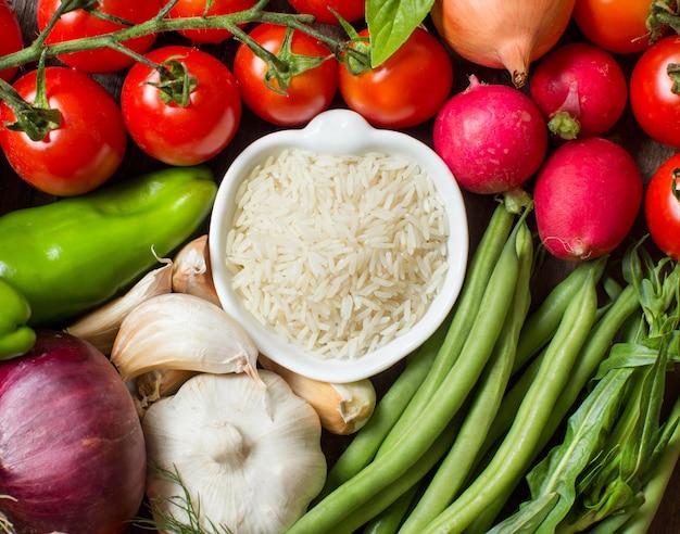 Рис басмати в миске между свежими свежими овощами