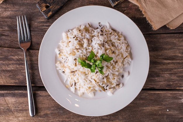 Basmati rice with herbs on a white plate on a wooden table
