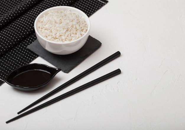 Белый шар с вареным органическим рисом жасмина basmati с черными палочками и сладким соевым соусом на бамбуковой циновке места на белой предпосылке.