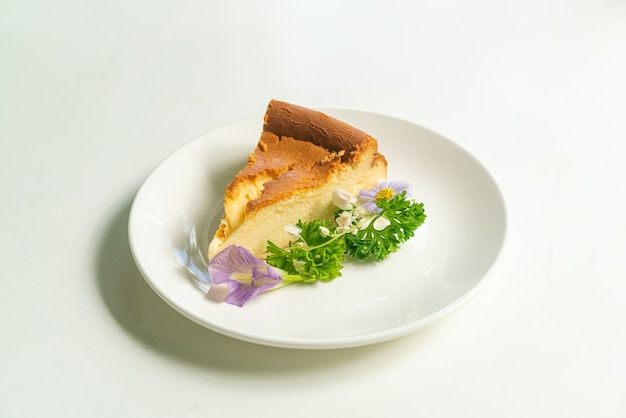 Basque burnt cheesecake decoratoin with flowers on white plate