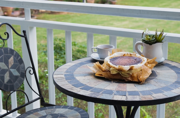 Basque burnt cheesecake with cup coffee on table on balcony with garden view.