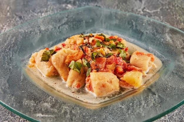 유리 접시에 소스에 회향 토마토와 바질을 곁들인 배스 생선