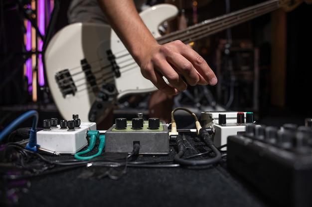 왜곡 효과 페달 세트가 있는 무대 위의 베이스 기타 연주자.