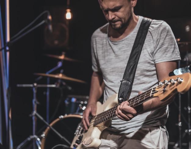 베이스 기타리스트는 흐릿한 배경의 어두운 방에서 베이스 기타를 연주합니다.