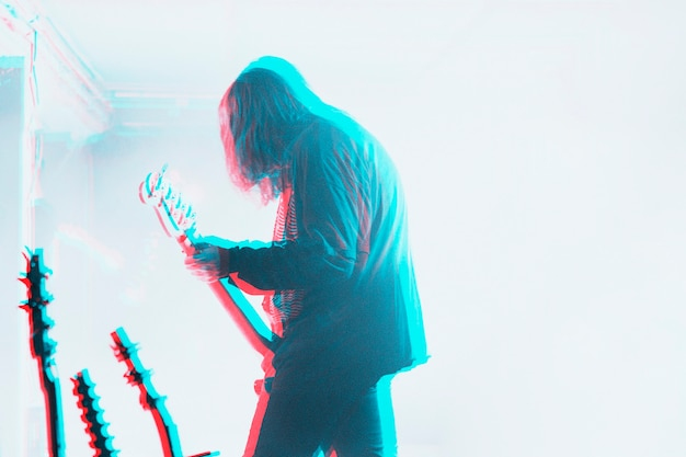 Bassist performing in a concert in double color exposure effect