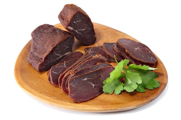 バストゥルマ、牛肉の乾燥テンダーロイン、薄くスライス、平らな木製の皿、白い背景で隔離。