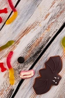 木製の背景にコウモリのクッキーとゼリーキャンディー。