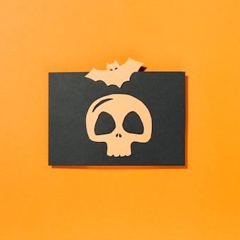 Pipistrello e teschio su un pezzo di carta nera