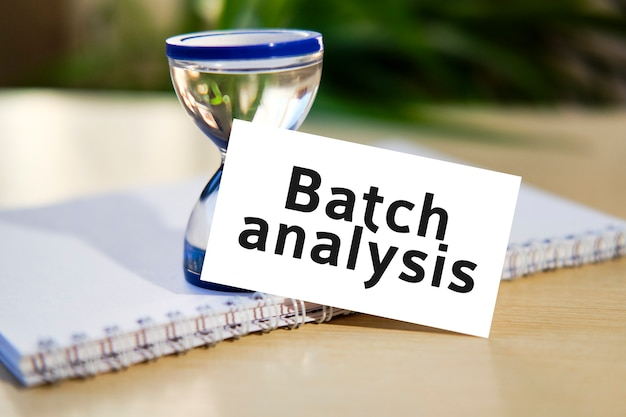 Batch analysis - business seo concept text on a white notebook and hourglass clock, green leaves of flowers