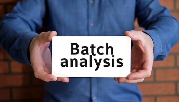 Batch analysis text in the hands of a young man in a blue shirt