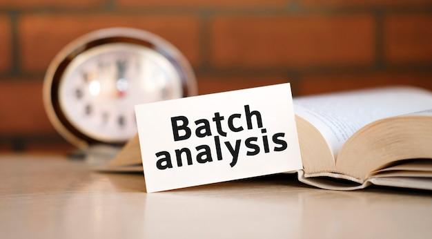 時計と開いた本と白い表面上のバッチ分析テキスト
