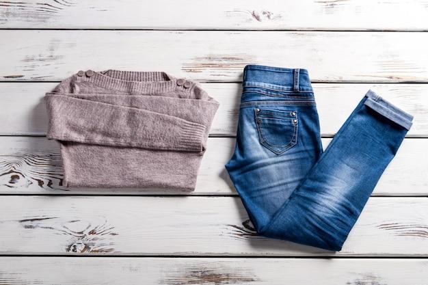 Bateau 네크라인 스웨터와 청바지. 선반에 청바지와 스웨터입니다. 청바지와 베이지색 스웨터. 선선한 날씨에 어울리는 여성복.