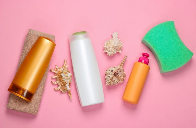 Bath accessories. bottles of shampoo with minerals, seashells, sponge, towel on a pink. hair care