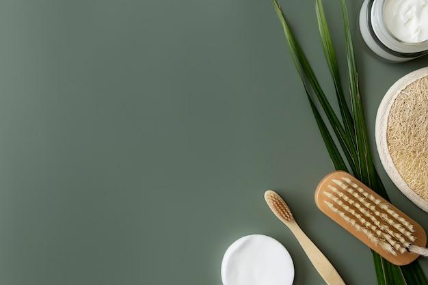 Банные принадлежности flay lay, пастельно-зеленый фон. концепция здравоохранения, пальмовый лист, деревянная зубная щетка, щетка для ног, ватные диски, мочалка. эко, без отходов, многоразовая концепция окружающей среды без пластика