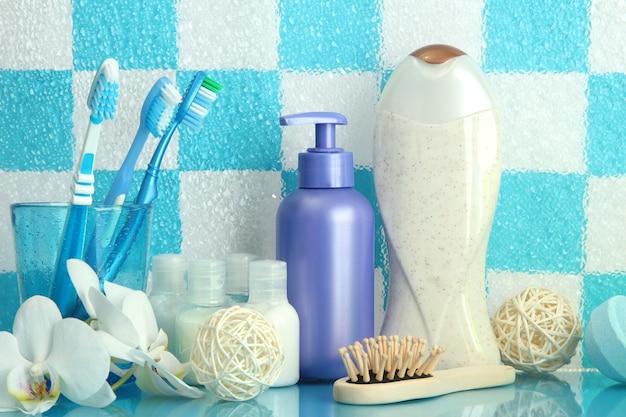 Банные принадлежности на полке в ванной комнате на поверхности стены синей плиткой