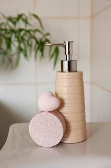 싱크대와 흐린 욕실 인테리어 배경에 목욕 세라믹 병, 비누 및 목욕 폭탄