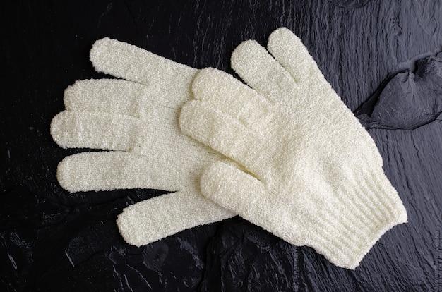 Bath massage gloves on black stone background