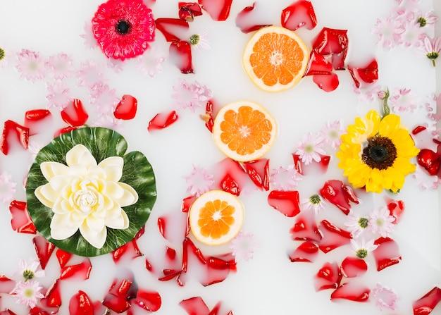 Latte da bagno decorato magnificamente con fiori, petali e fette di pompelmo