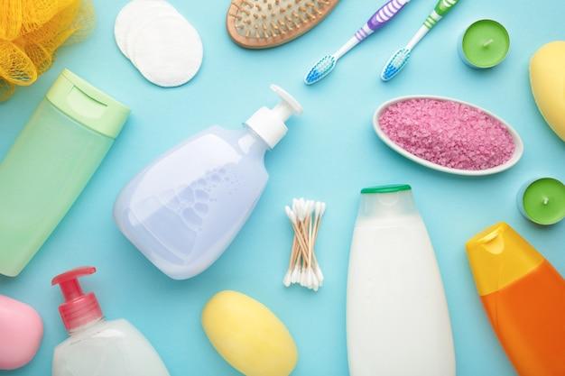 在蓝色墙壁上的浴产品。淋浴凝胶配芳香盐,肥皂和其他化妆品。顶视图