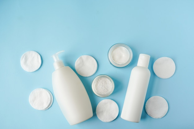 Bath products and cotton pads on blue background copy space