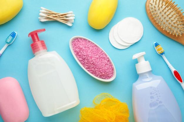 회색 배경에 목욕 제품. 아로마 소금, 비누 및 기타 세면 도구가 포함 된 샤워 젤. 평면도
